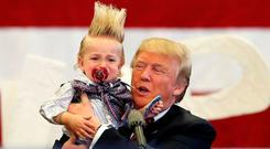 Donald Trump holds up a crying young child from the crowd as he arrives at a Trump campaign rally in New Orleans, Louisiana last March. REUTERS/Layne Murdoch Jr