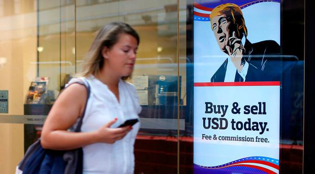 A woman walks past an advertisement featuring a cartoon of US President-elect Donald Trump at a currency exchange store in Sydney, Australia. Photo: David Moir/Bloomberg