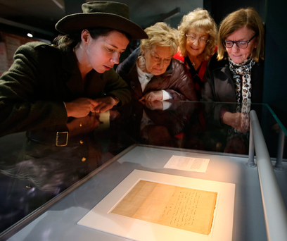 Sarah Kinlen dressed as a member of Cumann na mBan with Carmel O'Donoghue, Pauline McKenna and Teresa Quinn, look at a letter of surrender from Padraig Pearse at the GPO exhibition Photo: Gerry Mooney