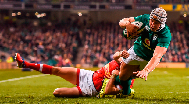 Luke Marshall scores Ireland's second try despite the attention of Gordon McRorie of Canada. Photo: Ramsey Cardy/Sportsfile