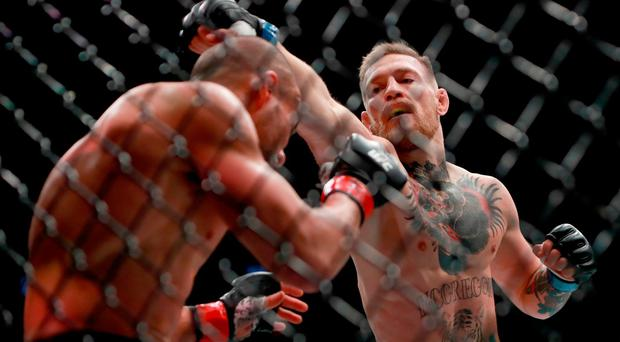 Conor McGregor of Ireland punches Eddie Alvarez in their UFC lightweight championship fight in their UFC lightweight championship fight during the UFC 205 event at Madison Square Garden