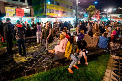 People wait in Te Aro Park in Wellington after being evacuated from nearby buildings following the earthquake. (Photo by Hagen Hopkins/Getty Images)