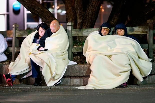 Guests of the Amora Hotel wrap themselves in blankets. (Photo by Hagen Hopkins/Getty Images)