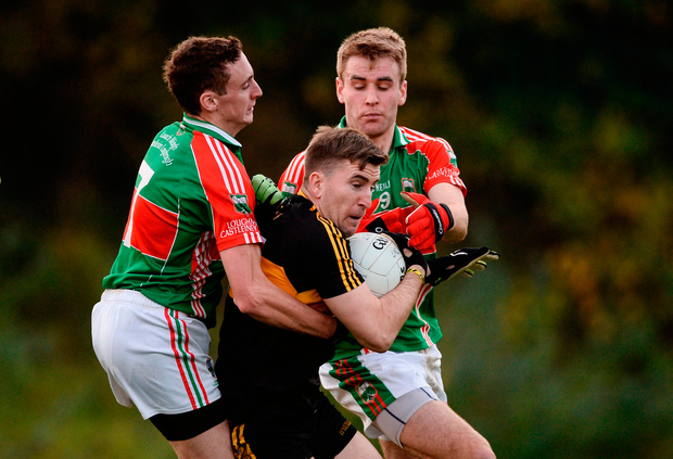 Mike Milner of Dr Crokes in action against Joseph Hennessy, left, and John McGrath of Loughmore Castleiney. Photo by Diarmuid Greene/Sportsfile