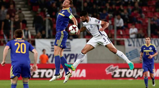 Greece's Giorgos Tzavellas and Bosnia and Herzegovina's Edin Dzeko in action