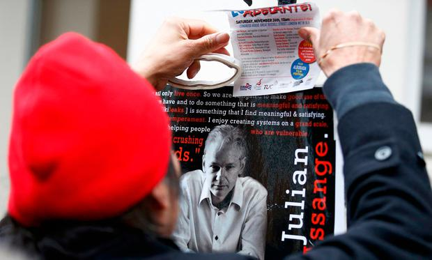 A supporter of Julian Assange holds a poster after prosecutor Ingrid Isgren from Sweden arrived at Ecuador's embassy to interview him in London, Britain, November 14, 2016. REUTERS/Peter Nicholls