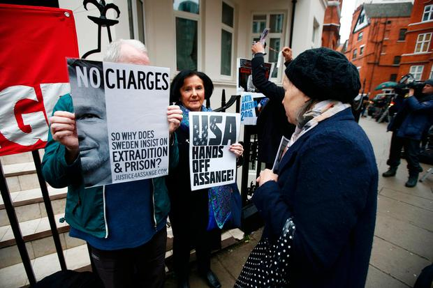 Supporters of Julian Assange hold posters after prosecutor Ingrid Isgren from Sweden arrived at Ecuador's embassy to interview him in London, Britain, November 14, 2016. REUTERS/Peter Nicholls