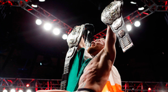 Conor McGregor celebrates with his featherweight and lightweight belts after defeating Eddie Alvarez