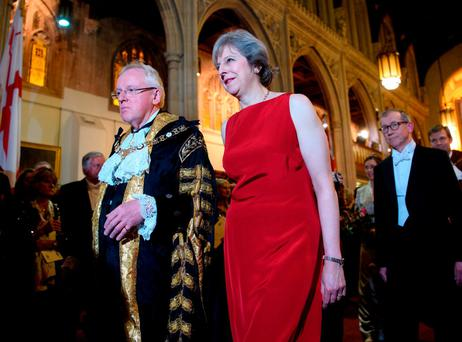 British Prime Minister Theresa May is accompanied by the Lord Mayor of London, Andrew Parmley, as she attends the Lord Mayor's Banquet at Guildhall last night. Photo: Carl Court/Getty Images