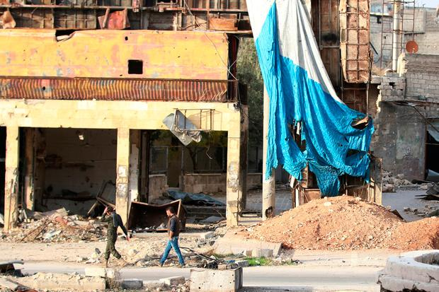 Men walk past a tarpaulin and damaged buses erected as protection from snipers in the rebel held area of Old Aleppo. REUTERS/Abdalrhman Ismail