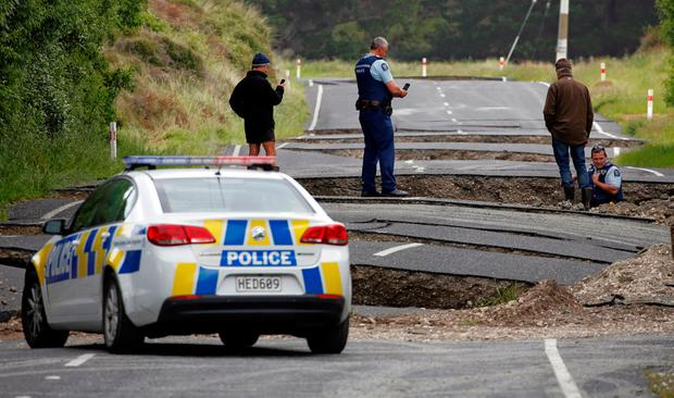 Policemen and locals look at damage following an earthquake, along State Highway One near the town of Ward, south of Blenheim on New Zealand's South Island. REUTERS/Anthony Phelps