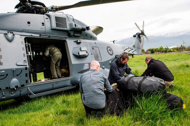 A Royal New Zealand Air Force NH90 helicopter delivers government officials and police to assess earthquake damage in Kaihoura on the upper east coast of New Zealand's South Island. REUTERS
