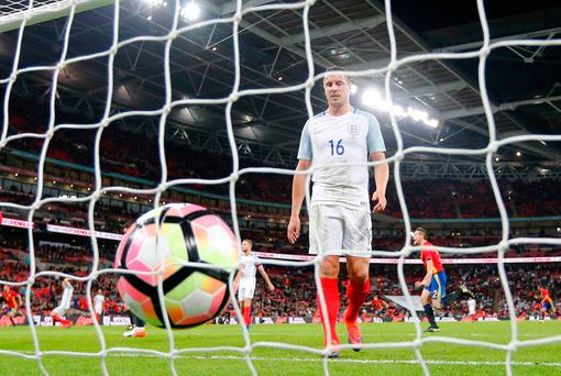 Phil Jagielka goes to lift the ball out of the net after England concede a late equaliser against Spain. (AP Photo/Frank Augstein)