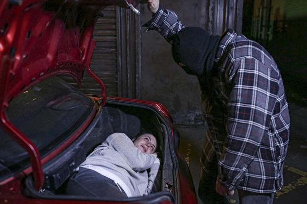 When Katy is unconscious he places her in the boot of his car.