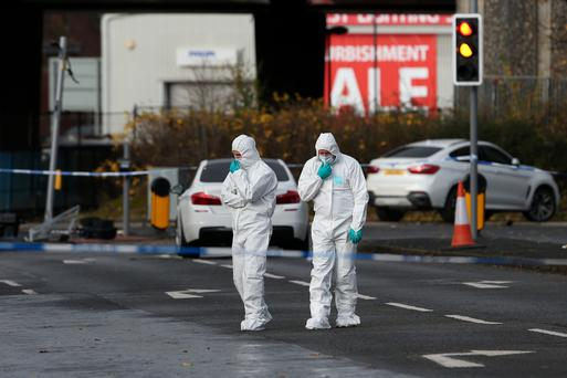 Police forensic officers at the scene where a man died after being shot as he sat in a car in Glasgow. Andrew Milligan/PA Wire
