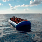 Refugees sit on a rubber boat off the Libyan coast earlier this month. Photo: Getty