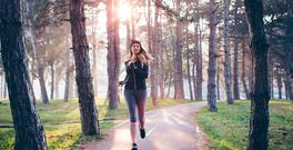 Woman jogging outside in sunny autumn forest.