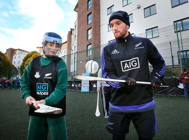 Noel Ryan (11) shows Aaron Cruden how to hurl at St Laurence O'Toole's on Sheriff Street. Photo: Frank McGrath