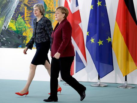German Chancellor Angela Merkel and Britain's Prime Minister Theresa May arrive for a statement prior to a meeting at the chancellery in Berlin