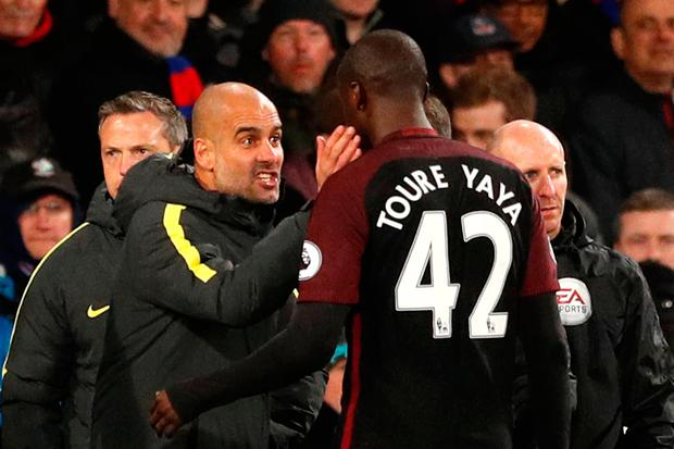 Manchester City manager Pep Guardiola speaks to Yaya Toure