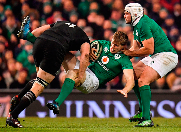 Andrew Trimble is tackled by Brodie Retallick during the Autumn International match at the Aviva Stadium yesterday. Photo: Sportsfile