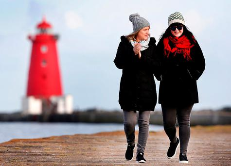 WRAPPED UP WARM: Ann Chadwick, from Raheny, and her daughter Ruth Chadwick, who lives on Dublin's North Circular Road, taking a stroll past Poolbeg Lighthouse during yesterday's frosty weather. Photo: Steve Humphreys