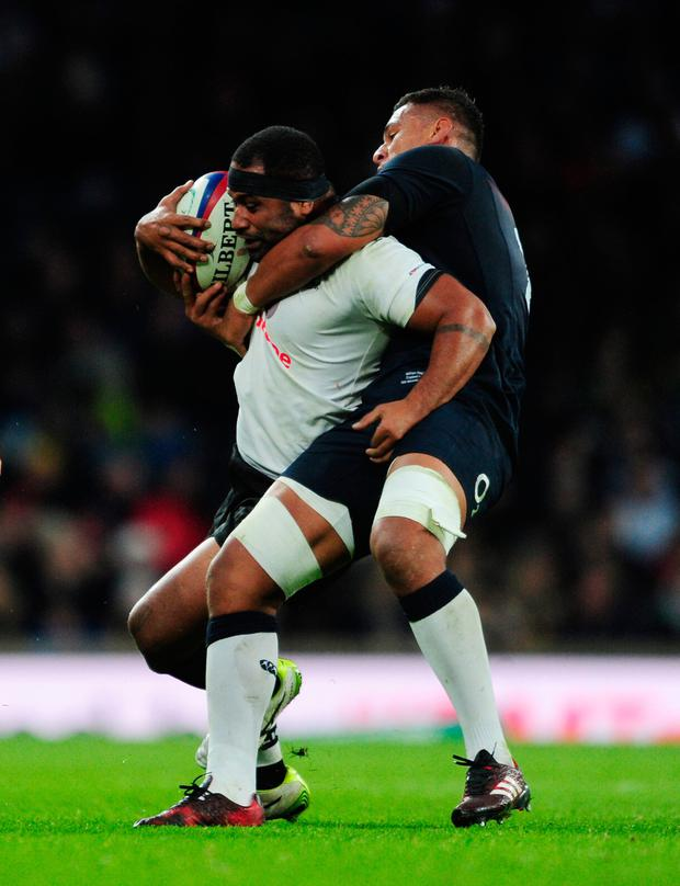 Tuapati Talemaitogo is tackled by Nathan Hughes during the Autumn International match between England and Fiji at Twickenham yesterday. Photo: Getty Images