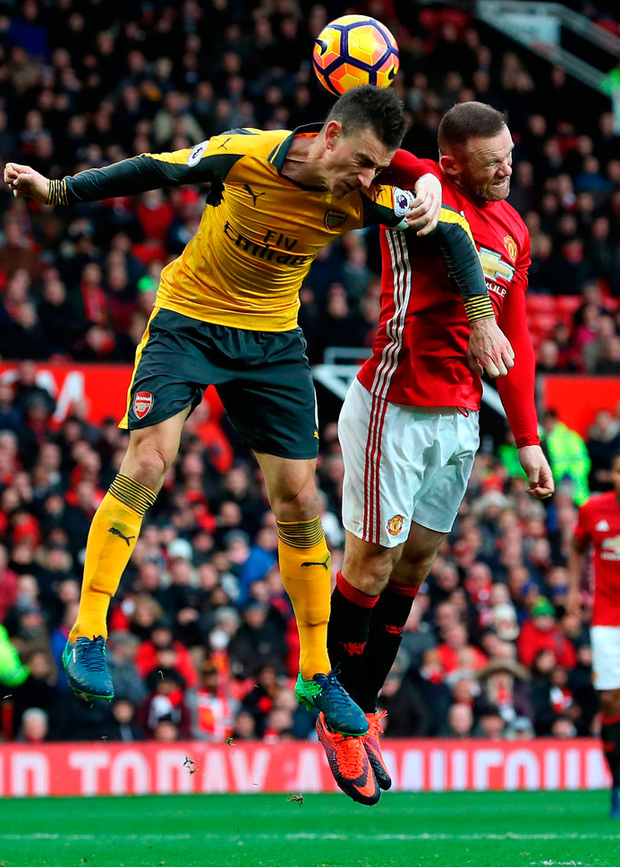 Manchester United's Wayne Rooney (right) and Arsenal's Laurent Koscielny battle for the ball during the Premier League match at Old Trafford. Photo: Martin Rickett/PA