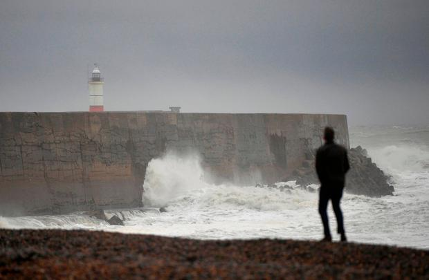 A man watches waves crash against the harbour wall as Storm Angus passes Newhaven in southern Britain, November 20, 2016. REUTERS/Hannah McKay