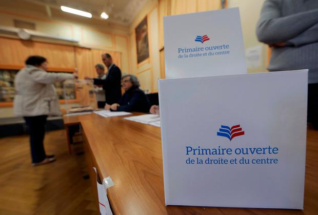 A woman casts her ballot in the first round of the French center-right presidential primary election in Nice, France, November 20, 2016. Sign reads,