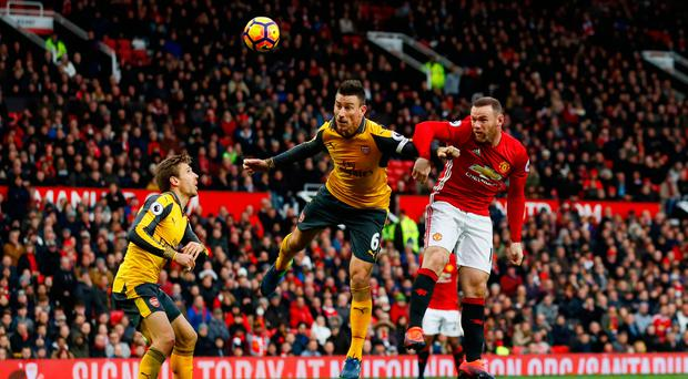 Manchester United's Wayne Rooney in action with Arsenal's Laurent Koscielny. Photo: Reuters / Jason Cairnduff
