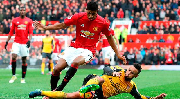 Manchester United's Marcus Rashford (left) and Arsenal's Francis Coquelin battle for the ball. Photo credit: Martin Rickett/PA Wire