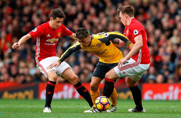 Arsenal's Mesut Ozil in action with Manchester United's Phil Jones and Ander Herrera. Photo: Reuters / Phil Noble