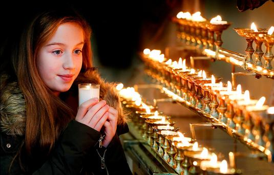 Abbey O'Donnell (11) lights a candle at the memorial mass for her Uncle Wayne O'Donnell, who died in a road accident in 2002 Photo: Steve Humphreys