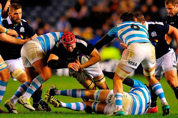 Scotland's lock Grant Gilchrist (C) is tackled by Argentina's lock Guido Petti Pagadizaval. Photo: Getty