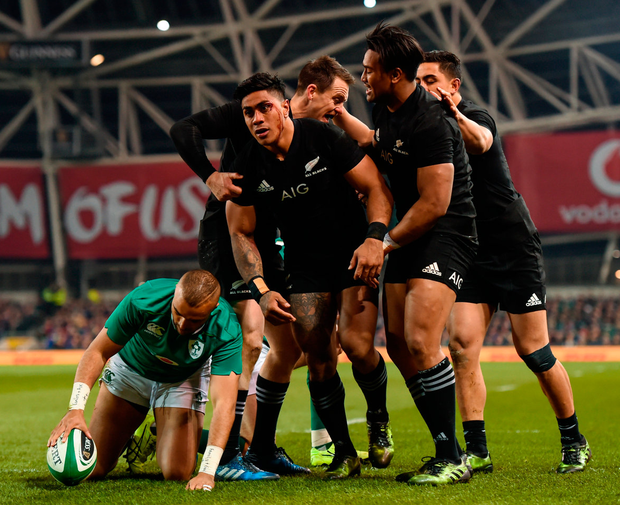 Malakai Fekitoa of New Zealand is congratulated by team-mates after scoring his side's first try during as Simon Zebo gathers the ball on the ground. Photo: Stephen McCarthy/Sportsfile