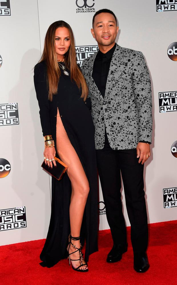 Chrissy Teigen and John Legend (R) arrive for the 2016 American Music Awards, November 20, 2016 at the Microsoft Theater in Los Angeles