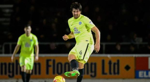 Peterborough United midfielder Michael Bostwick - and either a teammate or a steward behind him, who knows