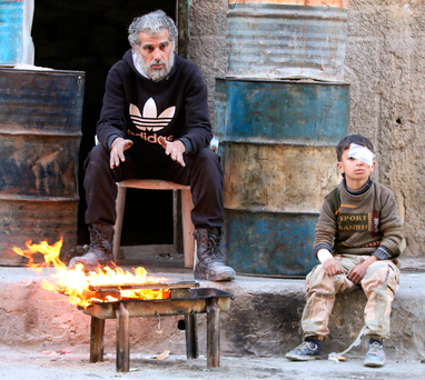 An injured boy and a man in a rebel-held area of Aleppo, Syria Photo: Reuters/Abdalrhman Ismail