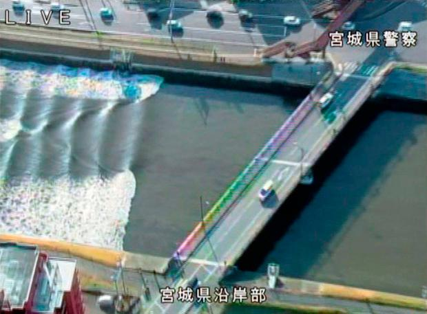 In this image made from video released by Miyagi Prefectural Police, the water flows up river in the Sunaoshi River in Tagajo, Miyagi prefecture, northern Japan, as a tsunami warning is issued following a strong earthquake Tuesday (Miyagi Prefectural Police/Kyodo News via AP)