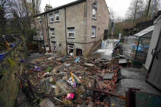 Flooding water flows past terraced houses in UK