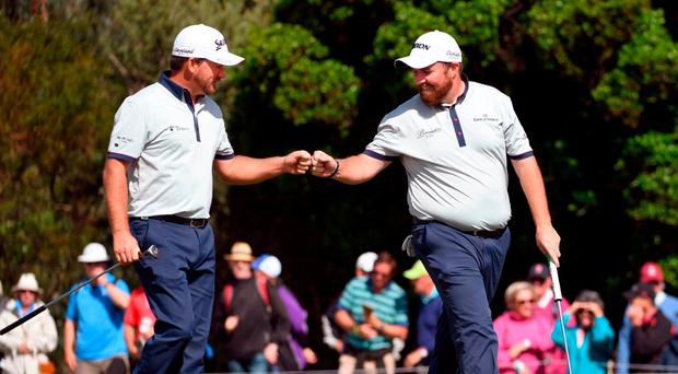 Graeme McDowell (L) and teammate Shane Lowry of Ireland bump fists during the first day of the World Cup of Golf on the Kingston Heath course in Melbourne