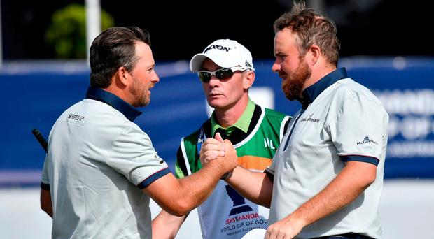 Ireland's Graeme McDowell shakes hands with teammate Shane Lowry, right, after their match at the World Cup of Golf at Kingston Heath in Melbourne, Australia