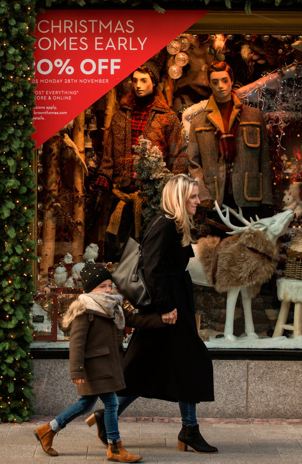 Shoppers walk past Black Friday signs on Grafton Street, Dublin Photo: Mark Condren