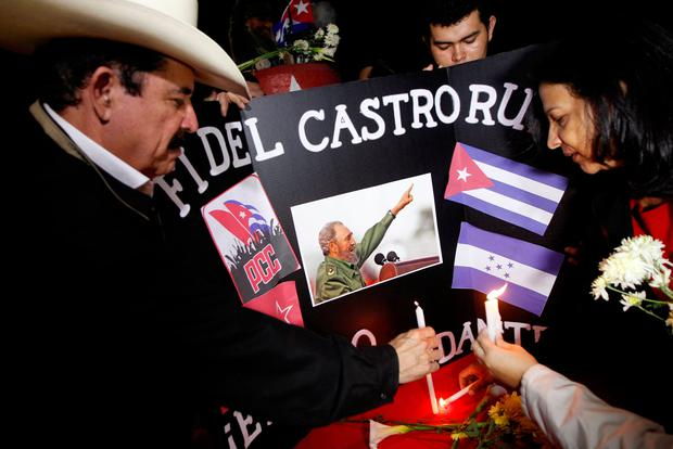 Honduras' former president Manuel Zelaya (2nd L) places candle beside a picture of Fidel, pay tribute, following the announcement of the death of Cuban revolutionary leader Fidel Castro, in Tegucigalpa, Honduras November 26, 2016. REUTERS/Jorge Cabrera