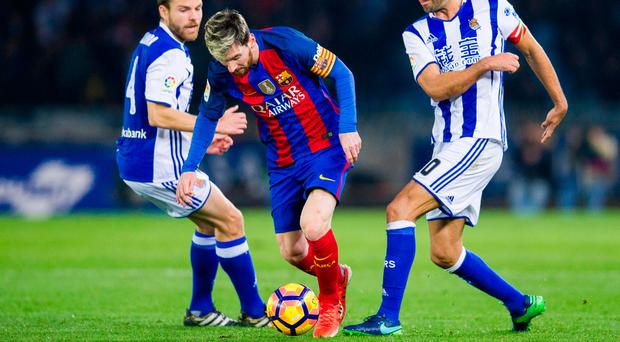 Lionel Messi of FC Barcelona duels for the ball with Real Sociedad's Asier Illarramendi and Xabier Prieto. Photo: Getty