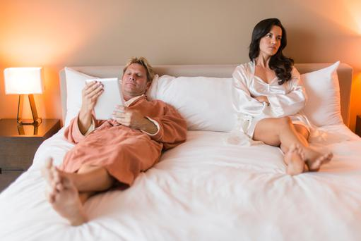 Man ignoring woman in bed