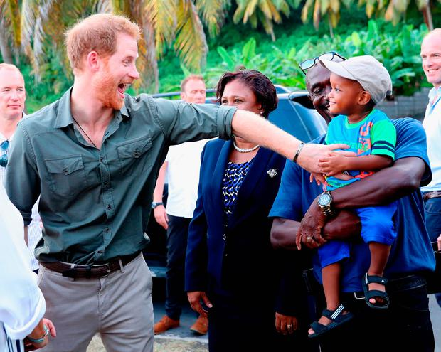 Prince Harry meets a young boy called Jyasi Junior as he visits a Turtle Conservation Project on the seventh day of an official visit to the Caribbean on November 26, 2016 in Colonarie, Saint Vincent and the Grenadines.