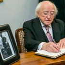 President Michael D Higgins and his wife Sabina signing the Book of Condolence for the late Fidel Castro at the Cuban Embassy on Pearse St Dublin. Photo: Kyran O'Brien