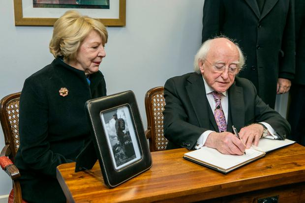 President Michael Higgins and his wife Sabina sign the book of condolence for the late Fidel Castro at the Cuban Embassy on Pearse Street, Dublin. Photo: Kyran O'Brien